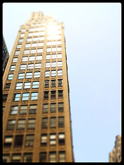 A Fuzzy Photo Of The Times Square Building With The Sun Glaring Of The Side.