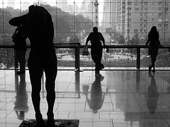 A Black And White Picture Taken Of Tourists Observing The Second Floor Of The Time Warner Building.