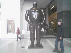 Man Standing Near Statue In Lobby Of The Time Warner Center.