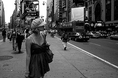 A Beautiful Young Woman Stares Into The Distance In Times Square