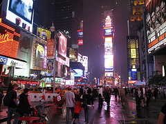 Pedestrian Traffic Amid The Illuminated Spectaculars And Jumbotrons Of Times Square.