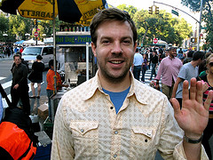 Tourist Waving To The Camera At Union Square, With Several People Walking Around The Area