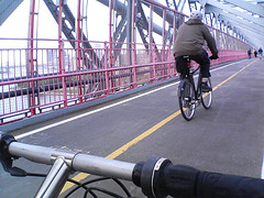 Biking Over The Williamsburg Bridge With The East River In The Background
