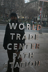 A Man On The Street Stares At His Reflection In A World Trade Center Sign